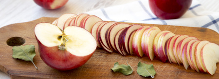 Slices of red apples on rustic wooden board, side view. Closeup.