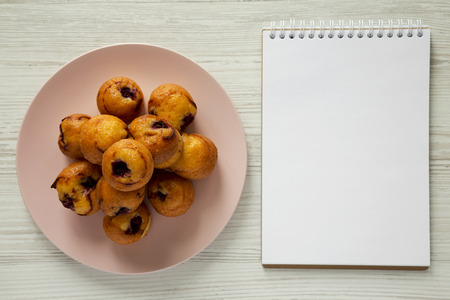 Top view, homemade mini muffins with cherry on pink plate, blank notepad over white wooden background. Overhead, from above, flat lay. 스톡 콘텐츠