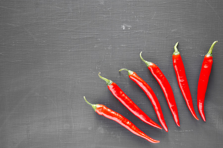 Hot red chili peppers on black background, top view. From above, overhead, flat lay. Copy space. Stock Photo