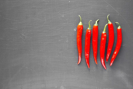 Hot red chili peppers on black surface, top view. From above, overhead, flat lay. Copy space.