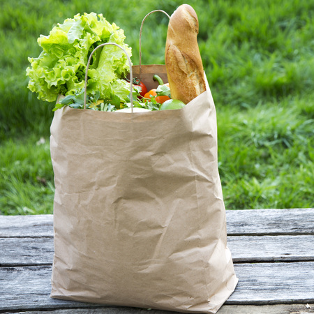 Various healthy food in paper bag on rustic wooden table. Side view. Close-up. Foto de archivo