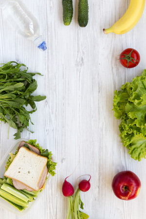 Lunch box and set of ingredients for making school lunch: vegetables, fruits, bootle of water on white wooden table. Healthy eating concept, overhead view.
