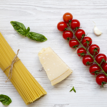 Spaghetti and various ingredients for cooking pasta on a white wooden table, from above. Flat lay. Top view, overhead.