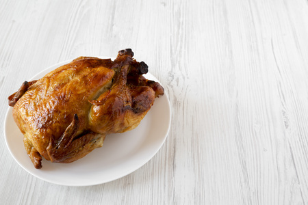 Homemade tasty rotisserie chicken on white plate over white wooden background, low angle view. Copy space. Foto de archivo