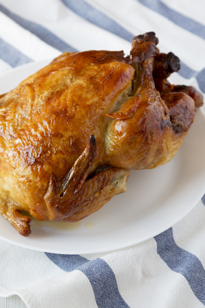 Homemade traditional rotisserie chicken on white plate, low angle view. Closeup. Stock Photo - 117927155