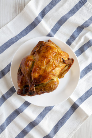 Homemade traditional rotisserie chicken on white plate, top view. Flat lay, overhead, from above.