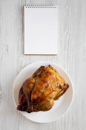 Homemade tasty rotisserie chicken on white plate, blank notepad over white wooden surface, top view. Flat lay, overhead, from above. Copy space.
