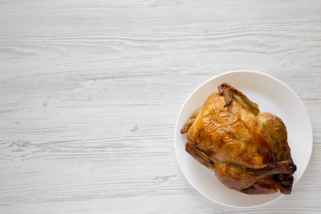 Homemade tasty rotisserie chicken on white plate over white wooden surface, top view. Flat lay, overhead, from above. Copy space.