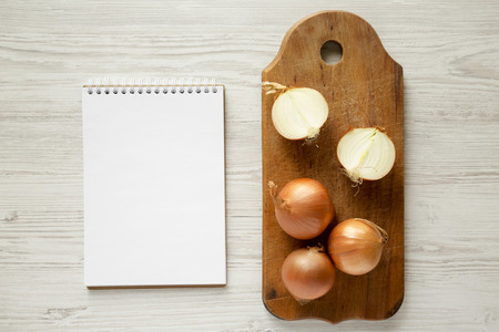 Unpeeled raw organic golden onions on wooden board, blank notepad over white wooden background, top view. Flat lay, overhead, from above. 版權商用圖片