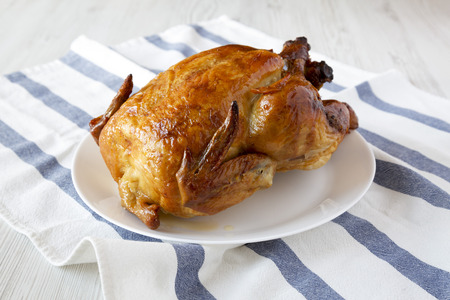 Homemade tasty rotisserie chicken on white plate, side view. Close-up.