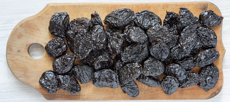 Dry prunes on rustic wooden board on a white wooden background, top view. Close-up. Flat lay, from above, overhead.
