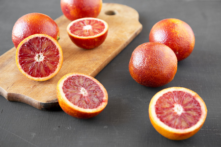 Whole and halved blood oranges on black background, low angle view. Close-up. 免版税图像