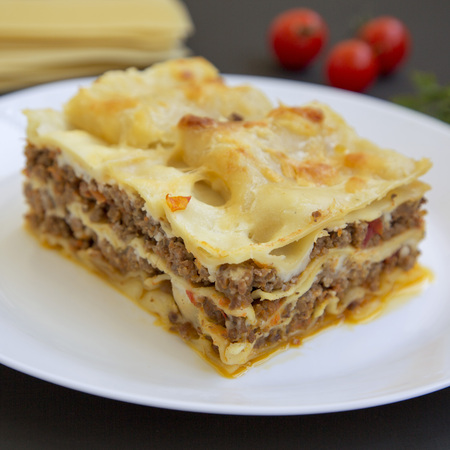 Traditional beef lasagne on a white round plate on black surface, side view. Close-up.