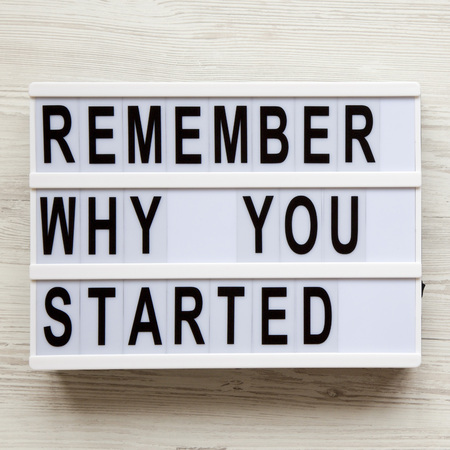 'Remember why you started' words on lightbox over white wooden surface, view from above. Top view, flat lay, overhead.