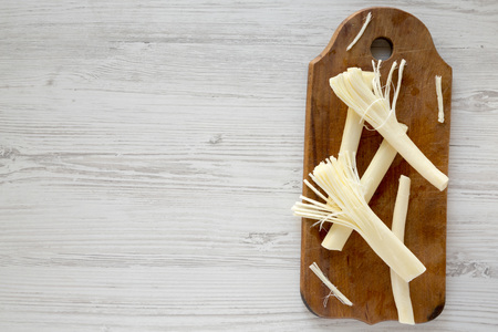 String cheese on rustic wooden board over white wooden surface, top view. Healthy snack. From above, overhead, flat lay. Copy space.
