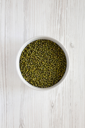 Green mung beans in a gray bowl over white wooden background, top view. Flat lay, overhead, from above.