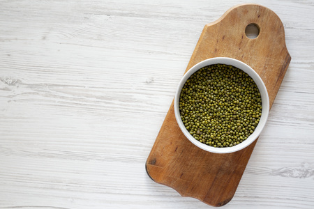 Green mung beans in a bowl on rustic wooden board over white wooden surface. Flat lay, overhead, from above. Copy space.