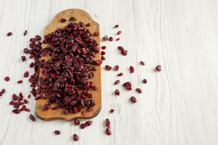 Dry organic cranberries on rustic wooden board over white wooden surface, low angle view. Copy space.