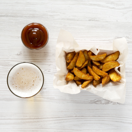 Fried potato wedges in paper box, barbecue sauce and glass of cold beer on a white wooden surface, top view. Close-up.