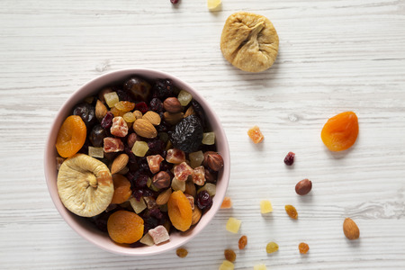 Dried fruits and nut mix in a pink bowl on white wooden background, top view. Overhead, from above, overhead. Archivio Fotografico