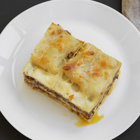 Traditional beef lasagne on a white round plate over black background, top view. Close-up. Foto de archivo