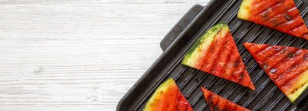 Slices of grilled watermelon in grilling pan on a white wooden table, overhead view. Healthy summer fruit. Top view, flat lay. Copy space.
