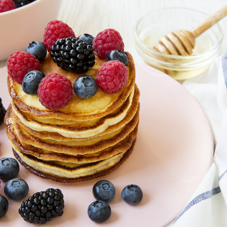 Homemade pancakes with berries and honey on a pink plate, side view. Close-up.