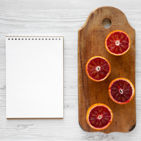 Blood oranges halved on rustic wooden board, blank notebook over white wooden surface, top view. Flat lay, overhead, from above. Imagens