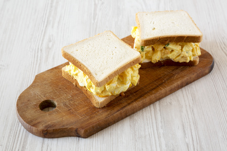 Homemade egg sandwich for breakfast over white wooden background, low angle view. Close-up.