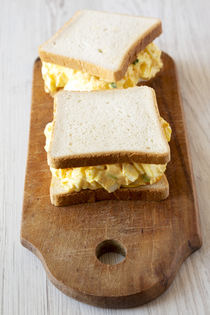 Homemade egg sandwich for breakfast over white wooden surface, low angle view. Close-up.