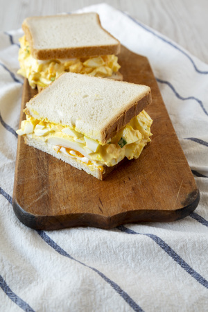 Homemade egg sandwich for breakfast on rustic wooden board, low angle view. Closeup.