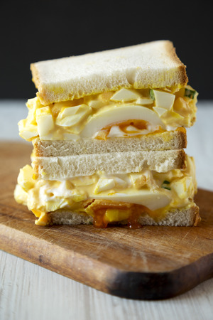 Homemade egg sandwich for breakfast on rustic wooden board, side view. Close-up. Stockfoto