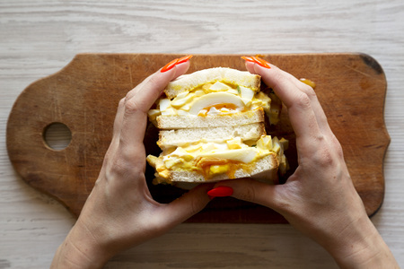 Female hands hold homemade egg sandwich, top view.