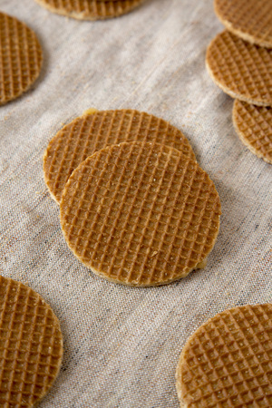 Sweet homemade dutch stroopwafels with honey-caramel filling on cloth, low angle view. Close-up.