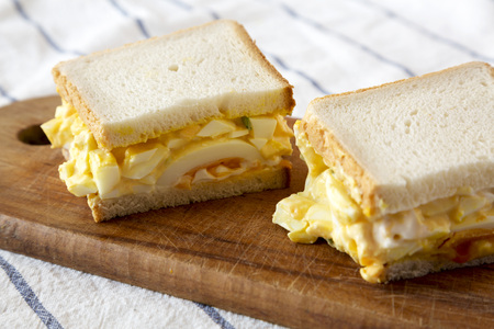 Homemade egg salad sandwich on wooden board, low angle view. Close-up.