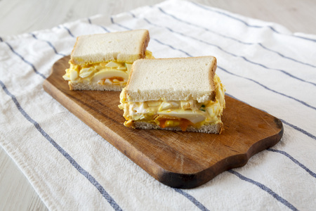 Tasty homemade egg salad sandwich on wooden board, low angle view.