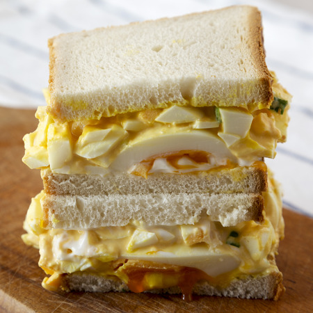 Delicious homemade egg salad sandwich on wooden board, low angle view. Close-up. Stockfoto