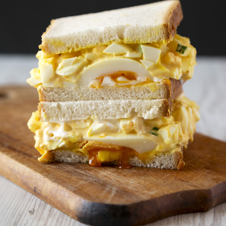 Homemade egg salad sandwich for breakfast on rustic wooden board, side view. Closeup. Stockfoto