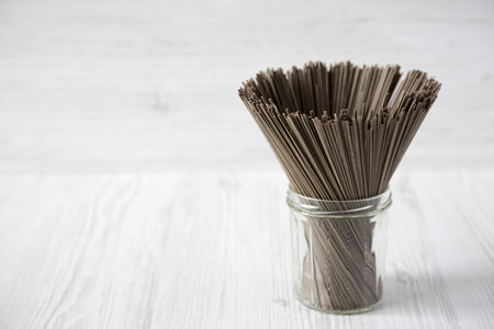 Organic buckwheat soba noodles in a glass jar on a white wooden background, side view. Copy space. 스톡 콘텐츠