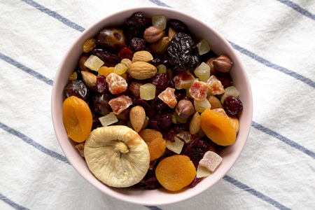 Dried fruits and nuts in a pink bowl, top view. Overhead, flat lay, from above.