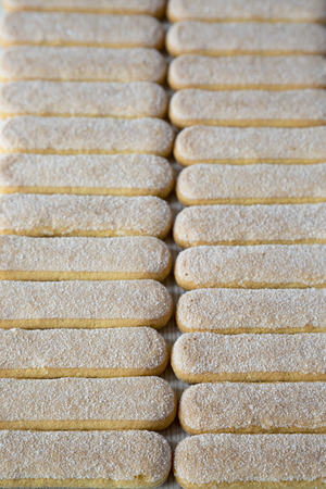 Savoiardi or ladyfingers cookies on a white wooden background, side view. 스톡 콘텐츠 - 120993105
