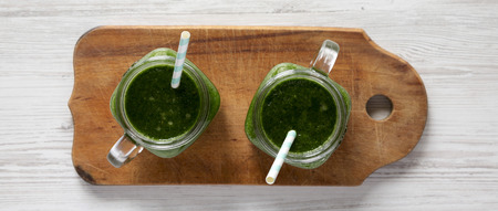 Green smoothie in glass jars on rustic wooden board over white wooden background, top view. Flat lay, overhead, from above.