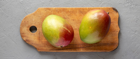 Sweet mangoes on rustic wooden board on gray surface, top view. Flat lay, from above, overhead. Standard-Bild