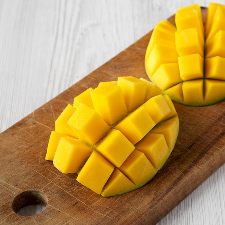 Fresh mango on rustic wooden board over white wooden background, low angle view. Closeup. Standard-Bild