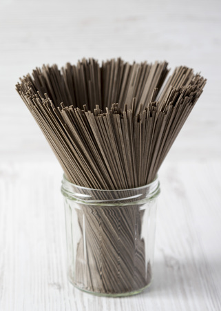 Organic buckwheat soba noodles in a glass jar over white wooden background, side view. Close-up.