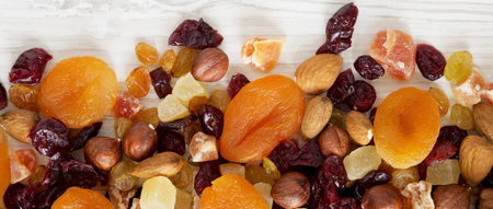 Dried fruits and nut mix on white wooden background, top view. Overhead, from above, flat lay.