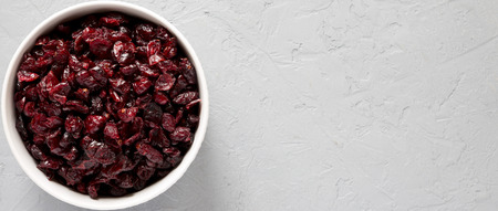 Dry organic cranberries in a bowl over gray surface, top view. Overhead, from above, flat lay. Copy space.