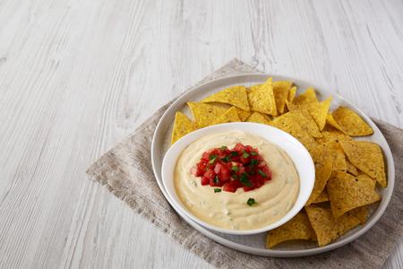 Salsa casera con queso en un tazón, chips de tortilla amarillos, vista lateral. Espacio para texto.