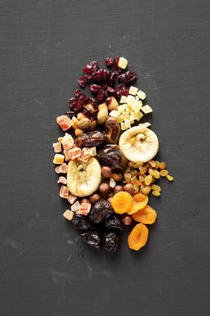 Dried fruits and nuts on a black table, top view. Overhead, from above.