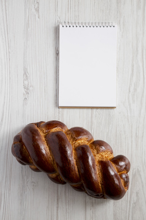 Homemade jewish challah bread and blank notepad on a white wooden background, top view. Copy space.